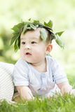 Portrait of a baby. An Asian baby is sitting on grass with a brach woven hat on head Stock Photography