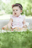 Portrait of a baby. An Asian baby is sitting on grass and smiling innocently Royalty Free Stock Photo