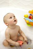 Portrait of a baby in the bathroom with toys for the bathroom royalty free stock image