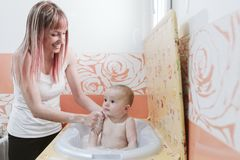 Portrait of a baby is being bathed by his mother using tub at home.  stock image