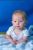 Portrait of a baby in a blue towel. On the green carpet Royalty Free Stock Photos
