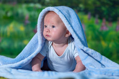 Portrait of a baby in a blue towel. On the green carpet Royalty Free Stock Images