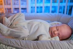 Portrait of a baby boy aged one month sleeping in a crib. Caucasian child in the childrens bedroom