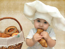 Portrait of a baby boy in a chefs hat with a basket of muffins and bagels Royalty Free Stock Photo