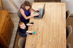 Portrait of baby boy sitting at table with woman using laptop at home Stock Images