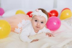 Portrait of a baby with brown eyes. The girl in the armband and dress is lying on the bed and wants to crawl, the child royalty free stock photography