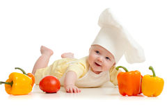 Portrait of a baby in chef hat with healthy  food. Portrait of a baby wearing a chef hat with healthy  food vegetables on white background Stock Photography