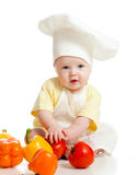 Portrait of a baby in chef hat with healthy  food. Portrait of a baby wearing a chef hat with healthy  food vegetables on white background Royalty Free Stock Photography