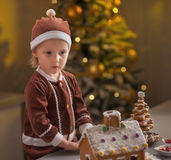 Portrait of baby with christmas cookie house. In christmas decorated kitchen stock image