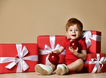 Portrait of a baby dressed a red bodysuit with red balls decorations on the xmas present gifts over beige nude studio background. stock photography