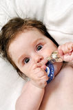 Portrait baby with dummy and silver toy. Closeup Stock Images