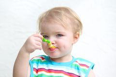 Portrait of baby eating porridge with spoon Stock Image