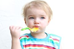 Portrait of baby eating porridge with spoon Royalty Free Stock Photos
