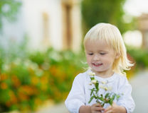 Portrait of baby with flowers outdoors Stock Image