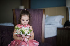Portrait of a baby girl on chair with a bright bouquet of flowers Stock Photography