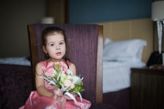 Portrait of a baby girl on chair with a bright bouquet of flowers Royalty Free Stock Images