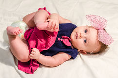 Portrait of a baby girl in a dress with diapers with a bow on her head which lies on the bed in her room Royalty Free Stock Photos