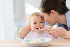 Portrait of baby girl eating lunch with her mother. Baby girl eating lunch with help of her mommy stock images