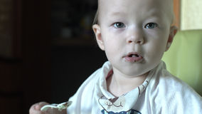 Portrait of baby girl eating porridge royalty free stock image