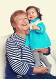 Portrait of baby girl and grandmother yellow toned. Happy family concept Stock Photos