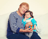 Portrait of baby girl and grandmother yellow toned Royalty Free Stock Photo