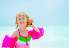 Portrait of baby girl listening sound of sea Stock Photos