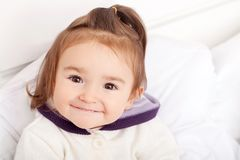Portrait of baby girl lying in bed under featherbed.  Stock Image