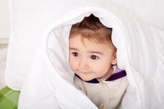 Portrait of baby girl lying in bed under featherbed.  Stock Photo
