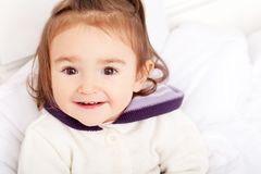 Portrait of baby girl lying in bed under featherbed.  Stock Photography