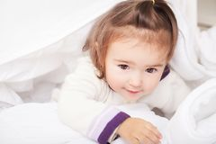 Portrait of baby girl lying in bed under featherbed.  Royalty Free Stock Images