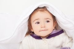 Portrait of baby girl lying in bed under featherbed.  Stock Photos