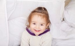 Portrait of baby girl lying in bed under featherbed.  Royalty Free Stock Photo