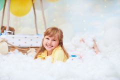 Portrait of a baby girl lying on a cloud next to a basket of balloon in the clouds, traveling and flying in dreams stock photos
