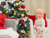 Portrait of baby girl near Christmas tree Stock Photos