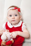 Portrait of baby girl in red dress playing with toy Stock Image