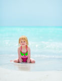 Portrait of baby girl sitting on sea coast Royalty Free Stock Image