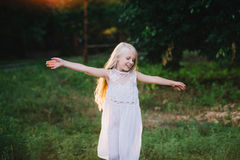 Portrait of a baby girl spinning in a field in sunset light Royalty Free Stock Photo
