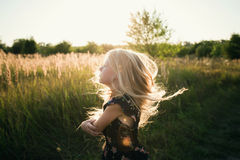 Portrait of a baby girl spinning in a field in sunset light Stock Photography