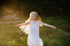 Portrait of a baby girl spinning in a field in sunset light Royalty Free Stock Images