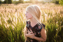 Portrait of a baby girl spinning in a field in sunset light Royalty Free Stock Photography