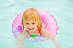 Portrait of baby girl with swimming in pool. Portrait of baby girl with swim ring swimming in pool royalty free stock photography