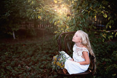 Portrait of a baby girl on vintage chair with a bright bouquet of flowers Royalty Free Stock Photos