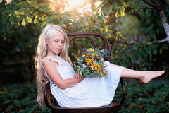 Portrait of a baby girl on vintage chair with a bright bouquet of flowers Royalty Free Stock Images