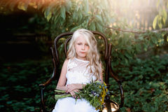 Portrait of a baby girl on vintage chair with a bright bouquet of flowers Royalty Free Stock Photography