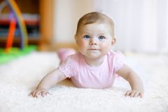 Portrait of baby girl in white sunny bedroom. Newborn child learning crawling. Royalty Free Stock Image