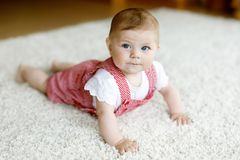 Portrait of baby girl in white sunny bedroom. Newborn child learning crawling. Stock Photo