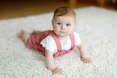 Portrait of baby girl in white sunny bedroom. Newborn child learning crawling. Royalty Free Stock Photos