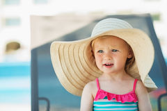 Portrait of baby in hat sitting on sunbed Royalty Free Stock Images