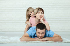 Portrait of baby and her parents lying on carpet in living room Royalty Free Stock Photo