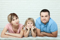 Portrait of baby and her parents lying on carpet in living room Stock Photography
